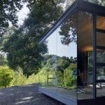 lovely small sillicon valley house design with glass siding and enclosure and door and black frame and wooden floor and ceiling and shady yard