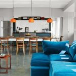 luxurious bright blue sofa design in the kitchen with orange shade pendants lamps and wooden table and chairs and white brick wall accent