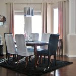 luxurious dining room design with white navy blue chairs and black area rug and wooden floor and peach curtain idea and stainless steel drum lamp shade