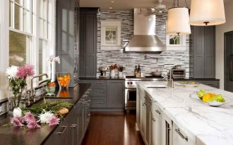 luxurious kitchen design with gray cabinet and marble black top and white island and pendant and stone backsplash and wooden flooring