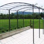 mediteranian wrought iron pergola painted in black plus garden with green grasses