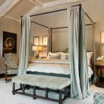 mesmerizing bedroom with iron canopy bed frame completed with curtain plus end bed bench plus comfy chairs and large area rug plus traditional chandeliers