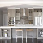 modern and luxurious gra kitchen cabinet idea with seating island and beige stools ad black glossy flooring idea with arched board and glass window