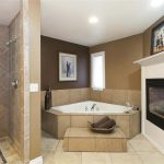 modern bathroom design idea with corner tub and fireplace and tile flooring and doorless shower idea and wall picture