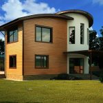 modern round two storey eco friendly house design with white paint and wooden siding and large grassy meadow