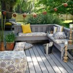 outdoor corner bench made of wooden with accented upholstery and wooden flooring for patios and ottoman plus beautiful garden lighting fixture