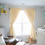patterned yellow and white blackout curtains nursery with white baby crib and wall mounted shelf and baby toys plus comfy chair