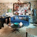 playful eclectic interior design with white turquoise wallpaper and white wing chair and blue sofa and wooden black table and sliding glass door