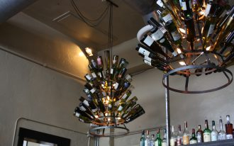 playful refined wine bottle chandelier idea with round tiered iron frame beneath white ceiling with gray shelves