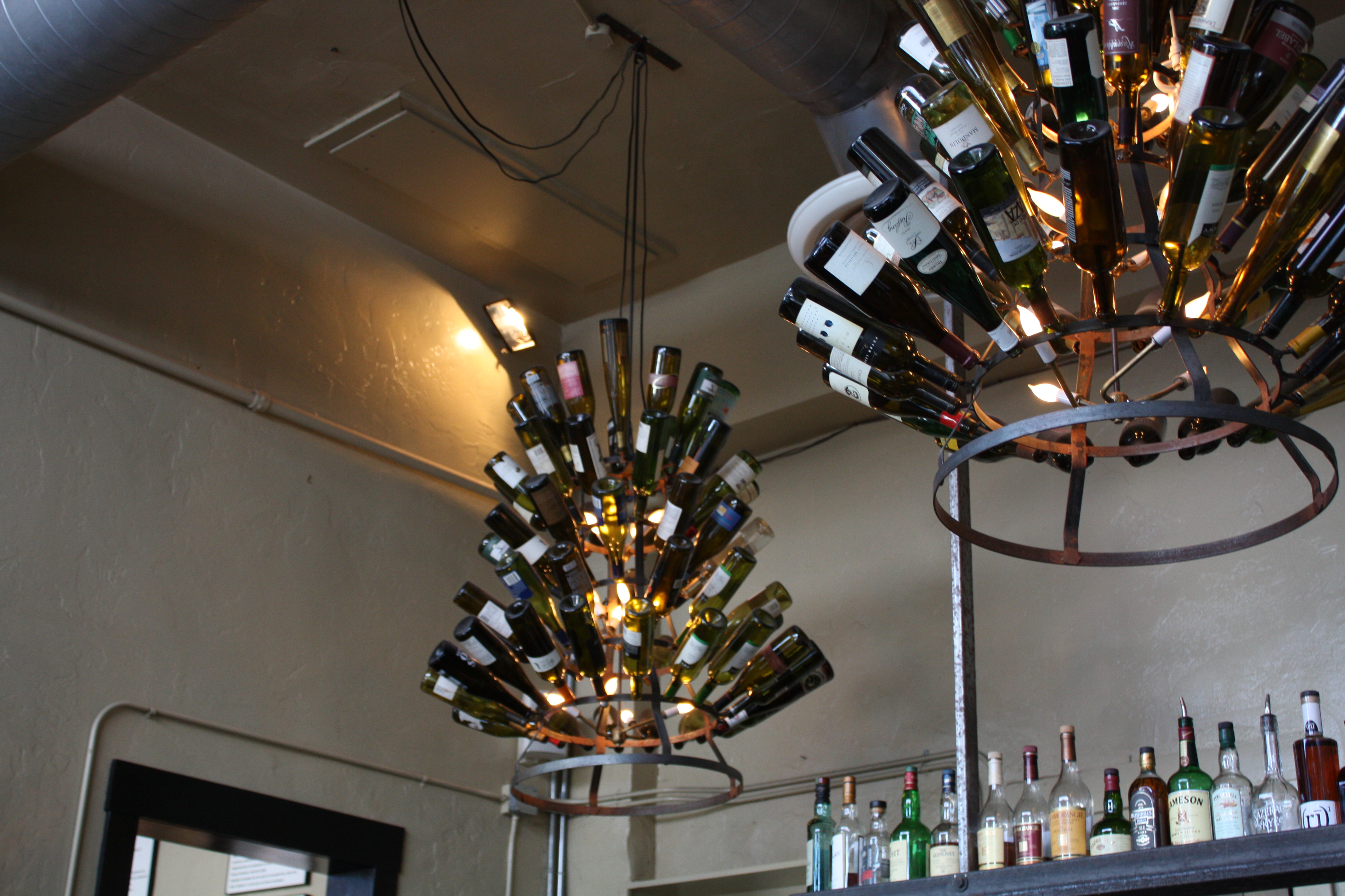 Playful Refined Wine Bottle Chandelier Idea With Round Tiered Iron Frame Beneath White Ceiling Gray
