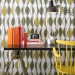 playful retro wallpaper design with leave shape and black glossy desk and yellow chair and orange case and black table lamp