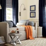 pottery barn daybed furniture in light grey color with monochromotic throw pillows an X base stool in grey medium sized area rug a pair of floor light fixtures