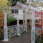 pretty wrought iron pergola in white with stunning decoration and lamp plus garden