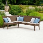 rattan outdoor corner bench with decorative cushion and concrete floor and natural garden behind