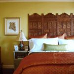 rustic cherry woode headboard design with carved style with white bedding and brown sheet and end table and yellow painted wall and picture