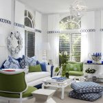 scandinavian stylish living room design with green white sofa and blue accent and arched glass window and white siding and floor cushions