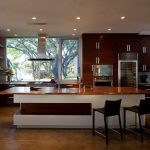 Serene Italian Kitchen Design With Concrete Painted Floor And Black Stools For Bar With Ceiling Lighting And Caramel Tone Top And Wooden Cabinet
