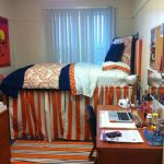 simple college dorm room idea with white bedding and orange stripe patterned sleeve and wooden desk and vanity and white sheer curtain and white siding