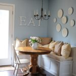 simple home banquette seating idea with round wooden table and white chair and wall picture and letter decoration and glass door