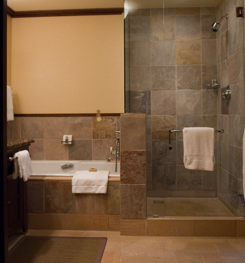 simple modern bathroom design with natural stone siding and doorless shower  design and white concrete tub
