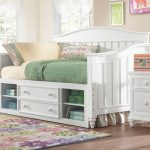 simple white trundle daybeds with storage and drawer with floral patterned rug and wooden floor and white wooden nightstand and green pastel bedding