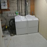 small basement laundry room idea with washing machine and brick wall and white flooring