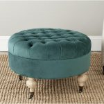 small round tufted turuoise ottoman with wooden leg featuring small wheels plus natural fiber rug