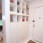 smart-entryway-wall-divider-in-white-from-ikea-expedit-shelves-framed-with-Millwork-for-storage-and-separate-hallway-with-bedroom
