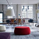 spacious interior with eclectic style with red coffee table and gray stools and white pendants and gray area rug and glass window
