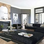 spacious living room design idea with gray wall paint and glass window and black couch and area rug and beige wooden board panel and wooden floor