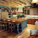spacious rustic kitchen design with retro big island in navy blue color with stools and exposed wooden beams on the ceiling with wooden floor