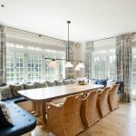 spacuous dining room design with navy blue banquette seating and beige rattan sofa and wooden table and track pendant and wooden floor and glass window