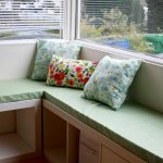 stunning bau window idea with modern drape and green banquette seating and floral cushions and storage