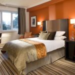 stunning bedroom color idea with orange accent in white space with stripe patterned area rug and white bedding with golden decoration and corner office desk and black curtain