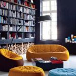 stunning bright yellow and blue sofa and pouff in home library with curver floor lamp and black wooden bookshelves and glass window