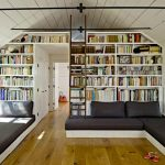 stunning large and tall bookcase idea in the loft living room design with black sofa design and wooden floor and lighting track