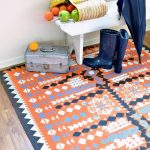 stunning patterned bohemian diy floor rug design with orange and navy blue design with white wooden bench with umbrella and boots