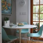stunning round white dining table with vintage soft blue chairs on wooden floor with glass door and wall painting