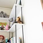 stunning white hanging bookshelves with wooden board and black rope on white painted wall with dolls