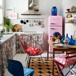 super bright retro dining table with wooden material and red blue chairs and pendant and white cabinerty with sleeve and pink refrigerator
