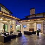super luxurious single storey house design with outdoor living space with fireplace and sofa design and paved patio deck