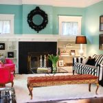 sweet blue eclectic interior design with fireplace and stripe patterned black and white sofa and bench and pink couch and white area rug