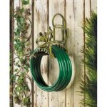 the-frog-garden-hose-holder-organizer-made-of-cast-iron-and-mounted-on-wooden-wall-and-smiling-frog-design-in-green-color