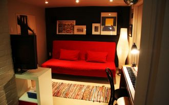 unique basement media room design with red ikea sofa bed design and piano with black chair and white storage divider and modern lighting