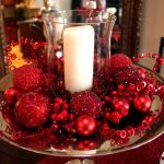 unique bowl for christmas centerpiece decoration idea with acrylic candle holder and balls and ribbon on red table cloth