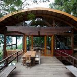unique shaped sustainable home design with curved wooden roof and wooden beams and glass window and wooden floor and outdoor dining set