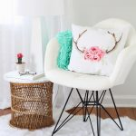 vintage white reading chair design with pink floral patterned cushion aside round rattan table with white sheepskin rug on wooden floor