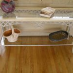vintage wrought iron sofa table with glass top table plus shelf beneath the table and laminate floor plus pretty basket