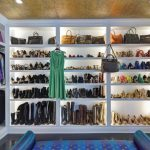 well organized walk in closet with white wooden cabinets and led closet lights plus blue rug