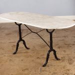 white marble bistro table with a pair of black wrought iron legs
